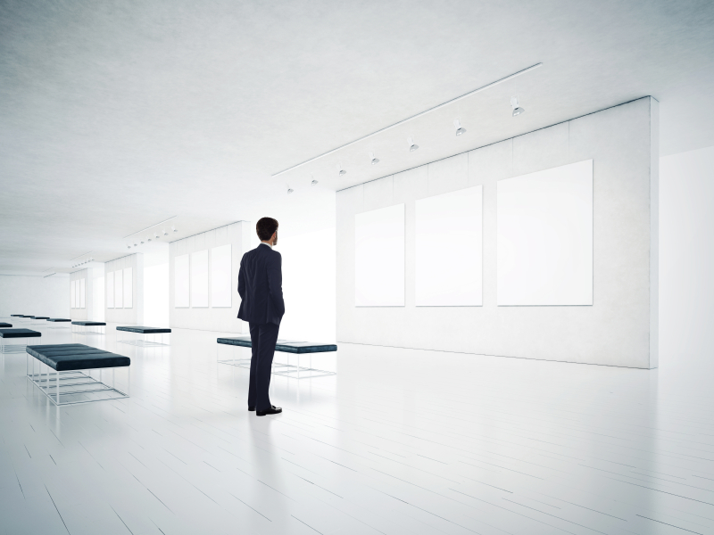 Gallery room and man looking at empty frames iStock_000044195132_Small