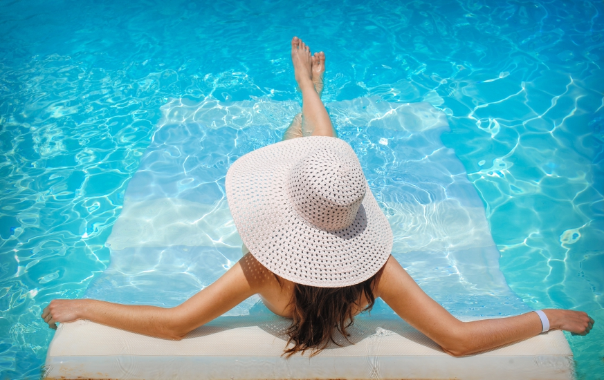 young woman in white hat resting in pool
