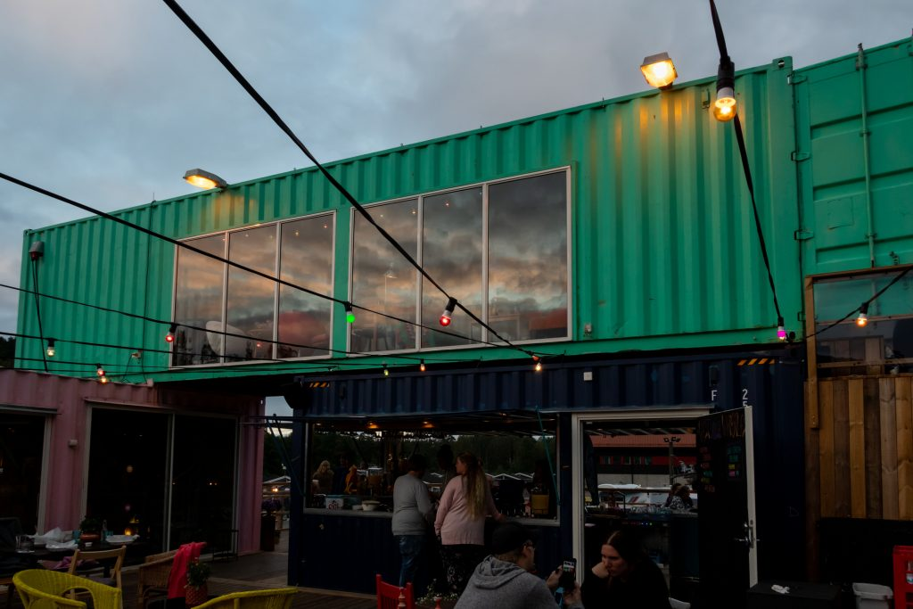 Outdoor front facade night view of a container pop-up restaurant with windows and a bar with people in Ullared Sweden.