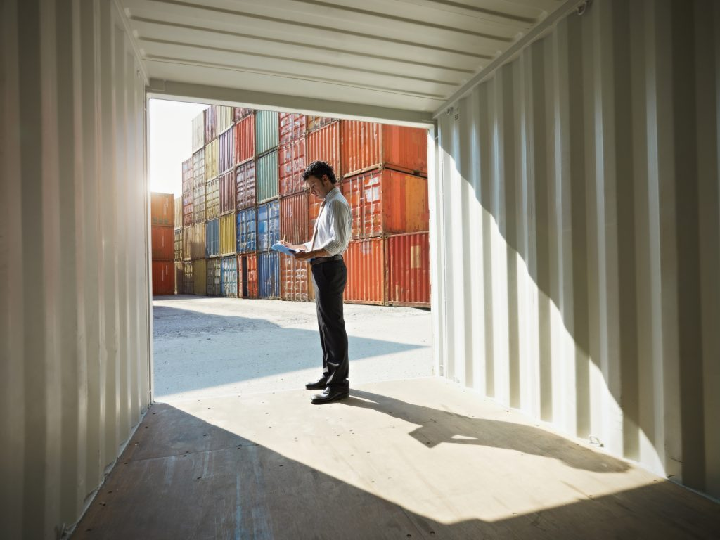 Businessman standing near cargo container and writing on clipboard.
